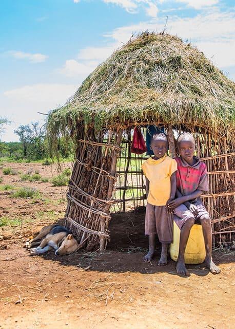 Young Kenyan children outside their hut